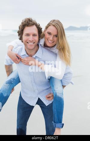 Portrait of a man piggybacking woman at beach - Stock Photo