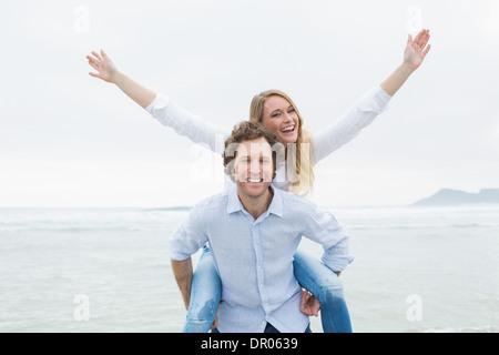 Man piggybacking woman at beach - Stock Photo