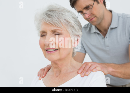 Male physiotherapist massaging a senior woman's neck - Stock Photo