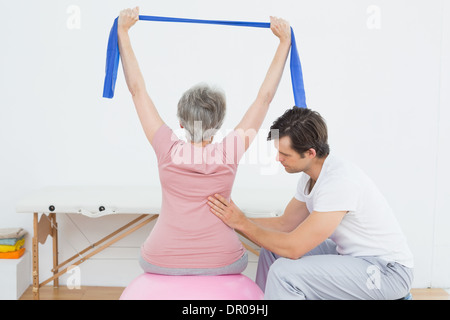 Senior woman on yoga ball with a physical therapist - Stock Photo