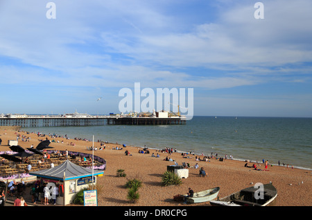 People relax on the pebbled beachfront next to Brighton Pier that has amusement activities, in Brighton city, East - Stock Photo