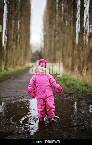 Little girl standing in puddle on tree lined path wearing pink. - Stock Photo