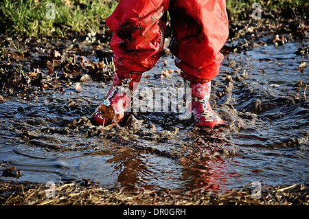 Child in wellington boots splashing in a puddle - Stock Photo