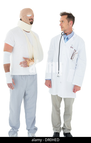 Doctor looking at a patient tied up in bandage - Stock Photo