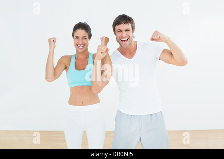 Cheerful fit couple clenching fists in fitness studio - Stock Photo