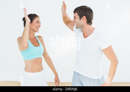 Cheerful fit young couple giving high five - Stock Photo