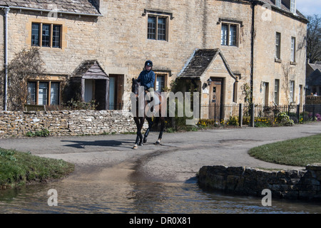 A horse rider in the Cotswolds village of Lower Slaughter. - Stock Photo