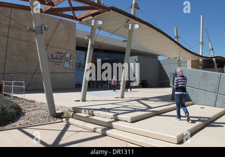 An Arab girl going to the entrance of the Children's Museum, situated within the Al Hussein National Park in Amman, - Stock Photo