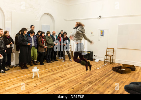 Performance Art - people watching a woman artist performing live art in a gallery UK - Stock Photo