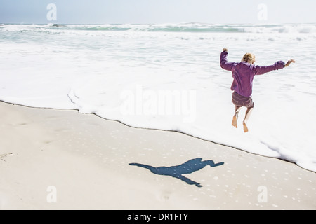 Girl playing in waves on sunny beach - Stock Photo