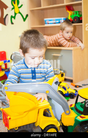 Two children play with toys at home - Stock Photo