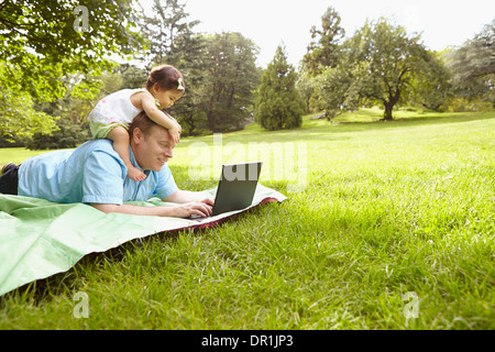Father and baby girl using laptop in park - Stock Photo