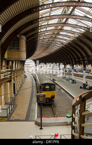 Interior view of trainshed with iron & glass roof, stationary trains & people waiting on platfom - York Railway Station, North Yorkshire, England, UK.