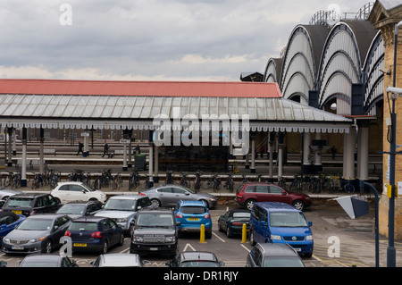 View of outside platforms, veranda, passengers walking & curved  windows of Victorian trainshed - York Railway Station, - Stock Photo