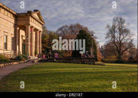People by impressive Yorkshire Museum, relax in beautiful, tranquil parkland, bathed in early evening sunlight  - Stock Photo
