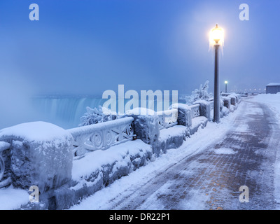 Sidewalk covered with snow and a lamp post, tranquil city scenery at Niagara Falls. Horseshoe waterfall wintertime - Stock Photo