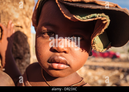 Portrait of face of Himba child with two hats on in Damaraland, Namibia, Africa - Stock Photo