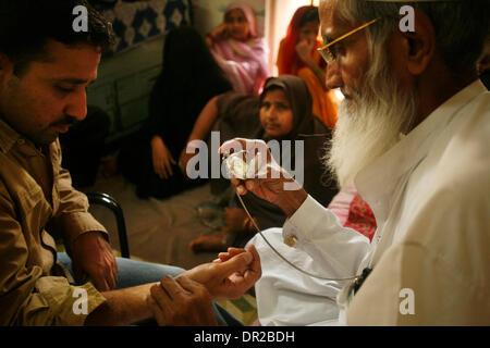 Jan. 12, 2009 - Amhedabad, India - A hakim takes the pulse of a man at his home in Ahmedabad, India.  A hakim is - Stock Photo