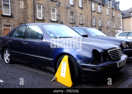 An old car with a flat tyre, missing lights and a DVLA clamp. - Stock Photo