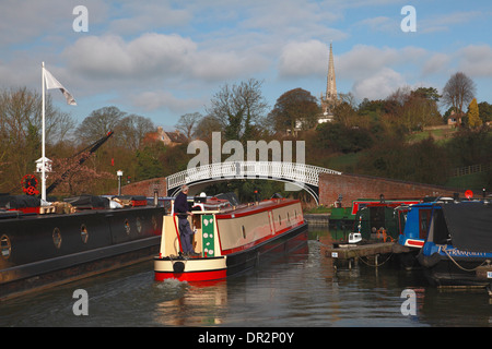 A narrowboat leaving Braunston marina on the Grand Union Canal and the spire of All Saints' Church, Braunston, Northants - Stock Photo