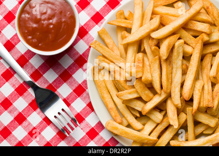 top view of french fries on plate with ketchup on checkered tablecloth - Stock Photo