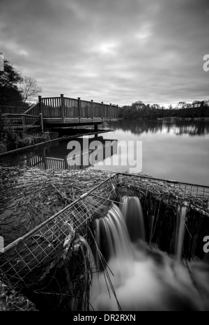 Black and white of small waterfall at Burton Mill Pond, West Sussex, UK - Stock Photo