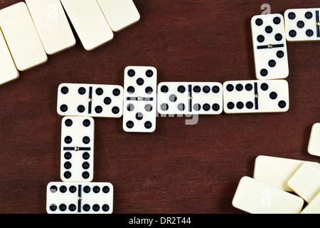 line of play in domino game on wooden table - Stock Photo
