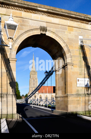 Bucks - Marlow on Thames - view through imposing  suspension bridge arch to All Saints church - bright sunlight - Stock Photo