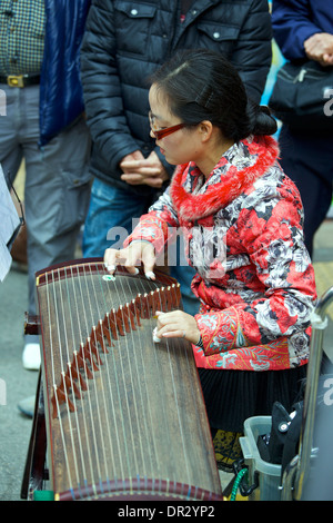 Young Oriental Woman plays A Chinese Zither to a crowd in Mong Kok, Hong Kong. - Stock Photo