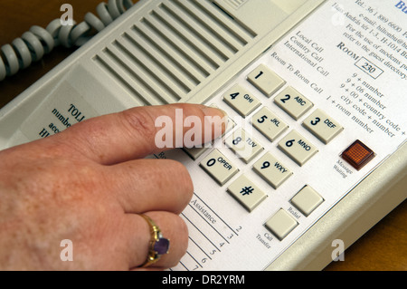 Female dialing on a hotel telephone. - Stock Photo