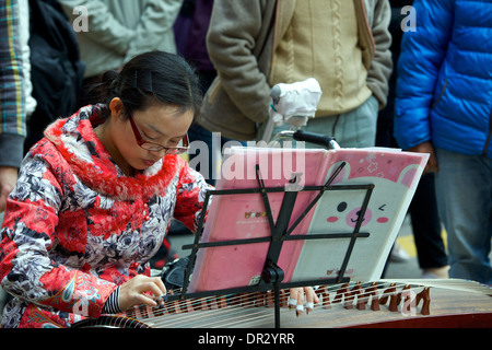 Young Chinese Woman plays A Chinese Zither (guzheng) to a crowd in Mong Kok, Hong Kong. - Stock Photo