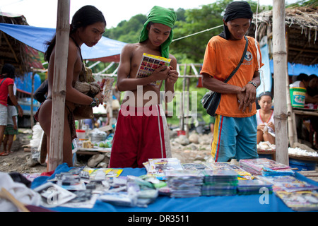 A Hanunoo Mangyans browse DVD titles for sale at a Mangyan market near Mansalay, Oriental Mindoro, Philippines. - Stock Photo