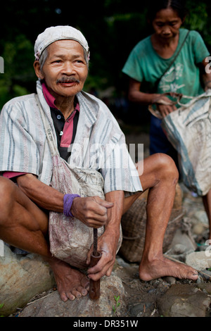 A Hanunoo Mangyan man mixes the ingredients for betel chew, or nga nga, in Oriental Mindoro, Philippines. - Stock Photo