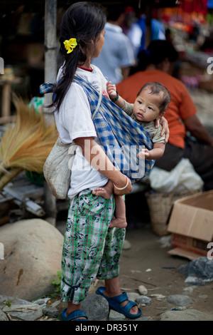 A Hanunoo Mangyan woman shops with her child at a Mangyan market near Mansalay, Oriental Mindoro, Philippines. - Stock Photo