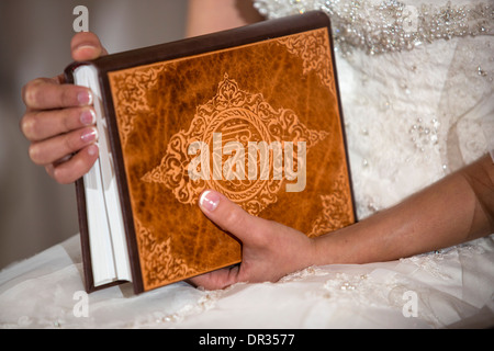 A bride holding a copy of the Koran during an Iranian wedding ceremony. - Stock Photo