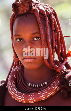 Portrait of Himba woman with traditional hairstyle outdoors in native villlage - Stock Photo