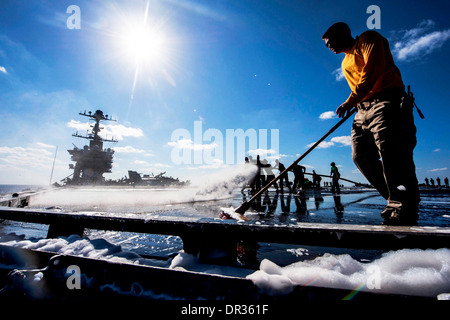 Sailors clean the flight deck of the aircraft carrier USS Harry S. Truman - Stock Photo