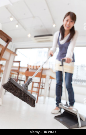 Young woman sweeping floor at café