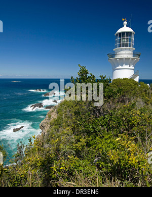 Historic Sugarloaf Point lighthouse on cliffs above turquoise water and wild sea at Seal Rocks Great Lakes region - Stock Photo