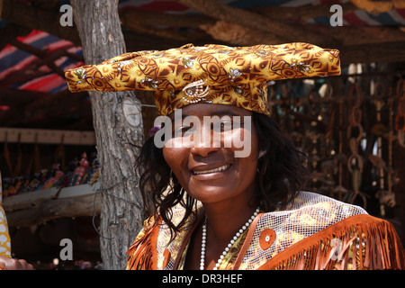 Herero tribal woman in her traditional Victorian dress ,wearing the typical 'horn hat',in Namibia.Africa. - Stock Photo