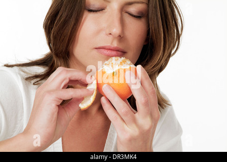 Woman sniffing an orange - Stock Photo