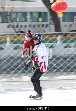 Beijing, China. 19th Jan, 2014. A foreigner skates while holding a child at an ice rink of Shishahai Lake in Beijing, - Stock Photo