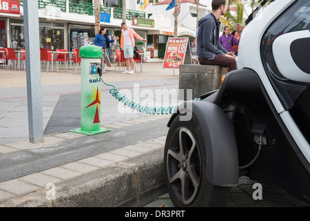 Renault Twizy battery-powered electric car plugged in to a Sol-lar battery charging point on roadside in Canary - Stock Photo