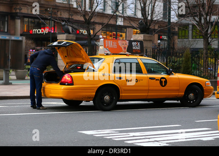 A NYC taxi outside Macy's in Herald Square, Manhattan - Stock Photo
