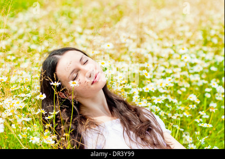 woman with closed eyes relaxes in daisies - Stock Photo