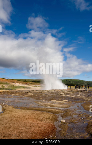 Group of tourists watching an eruption of the geyser Strokkur in Haukadalur, Iceland. - Stock Photo