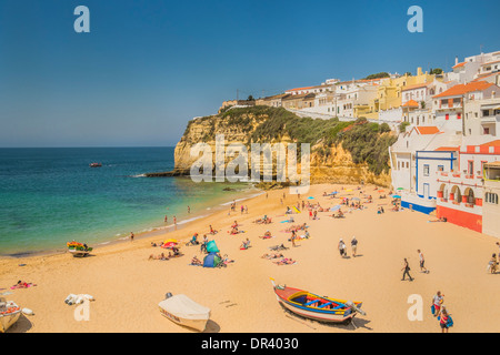 people on the beach, in the background houses built on the rock, carvoeiro, algarve, portugal - Stock Photo