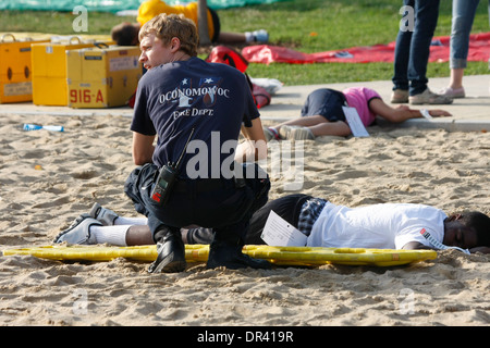 An EMT at a scene of a mass casulty exercise helping on one of the victims - Stock Photo