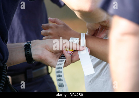 An EMT putting on patient tracking tag on victims at a mass casualty incident - Stock Photo