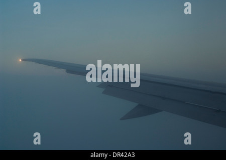 Plane flying through clouds while on approach into San Francisco, California - Stock Photo